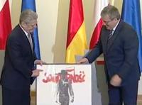 Der polnische Präsident Bronislaw Komorowski (rechts) schenkt Bundespräsident Joachim Gauck ein Wahlplakat der Solidarnosc aus dem Wendejahr 1989.